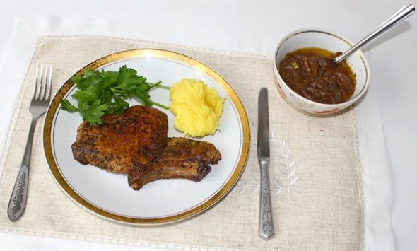 Котлета с косточкой, обжаренная на сковороде, картофельное пюре и помидор на тарелке