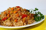 Тарелка с гречневой кашей, кусочками мяса, моркови, красного перца и зеленью