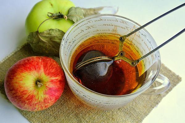 Чай из листьев яблони в прозрачной чашке, рядом лежат яблоки