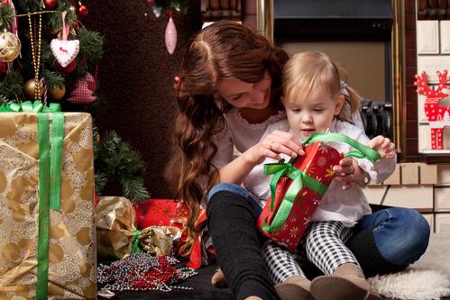 Мама с маленькой дочкой разворачивают новогодние подарки