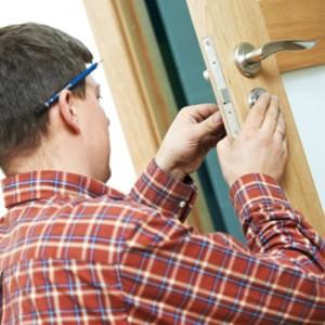 Плотник вставляет замок в двери