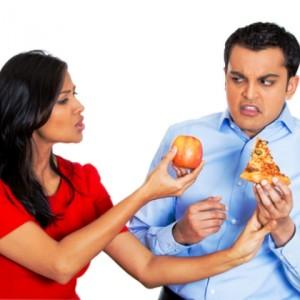 Женщина предлагает мужчине яблоко вместо пиццы, которую тот держит в руках. Весь облик мужчины выражает отвращение.