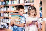 Мальчик со стопкой книг и девочка с ридером