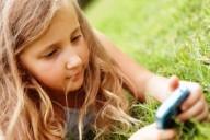 Длинноволоса девочка с мобильным телефоном в руках лежит на траве