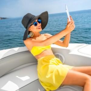 Девушка в синей шляпе и желтом платье на катере в открытом море с гаджетом в руках