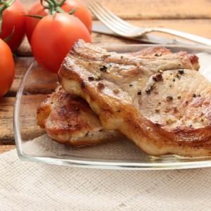 Котлета с косточкой на прозрачном блюде, рядом лежат помидоры