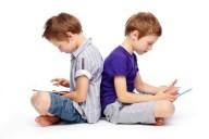 Два мальчика-близнеца склонились над своими гаджетами