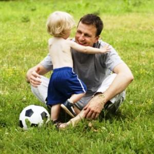 Маленький светловолосый мальчик обнимает счастливого отца