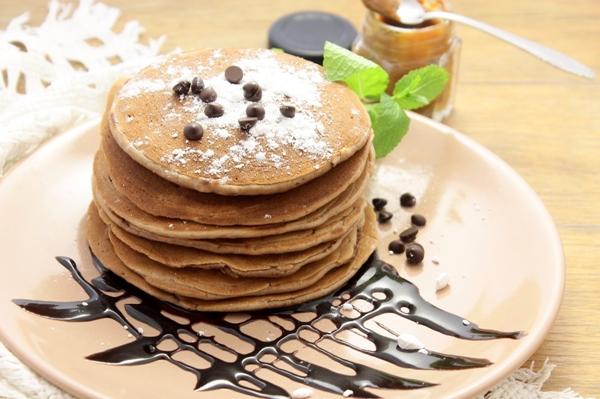 Фото шоколадных панкейков с кусочками шоколада и сахарной пудрой на розовой тарелке