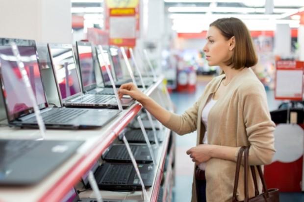 Молодая женщина выбирает монитор компьютера