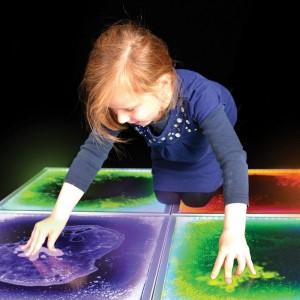 Девочка прикасается руками к жидкой наполно плитке