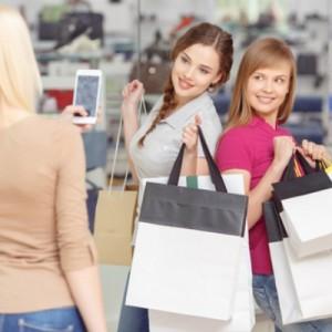 Три красивые девуши со смартфоном делают покупки