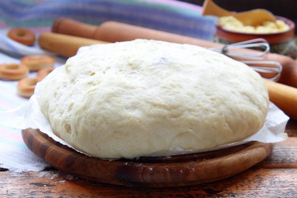 Дрожжевое тесто на круглой деревянное доске