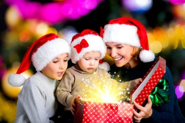 Мама и двое детей в новогодних костюмах распаковывают подарки