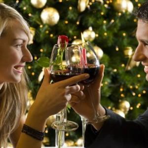 Романтическая пара влюбленный с бокалами шампанского ужинает на фоне новогодней елки