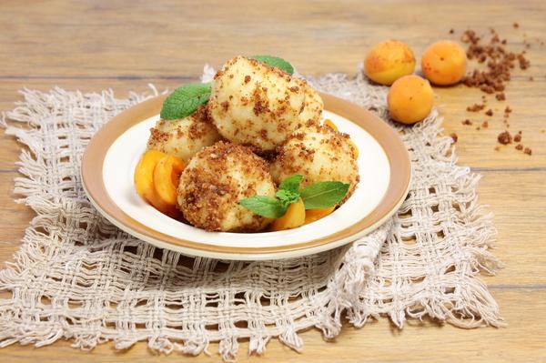 Творожные кнедлики с абрикосовой начинкой на тарелке