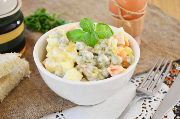 Готовый картофельный салат с зеленым горошком, украшенный петрушкой