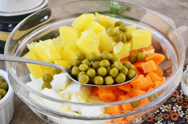 Нарезанные яйца, морковь, картофель и зеленый горошек в прозрачной миске