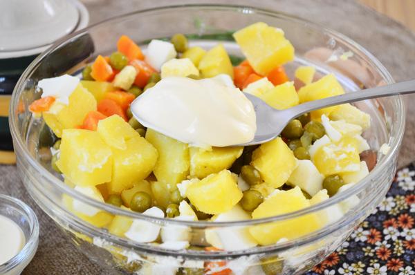 Нарезанные картофель, морковь и зеленый горошек с ложкой майонеза