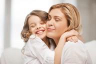 Девочка школьного возраста кремкого обнимает свою молодую мать