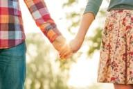 Влюбленные парень с девушкой держатся за руки