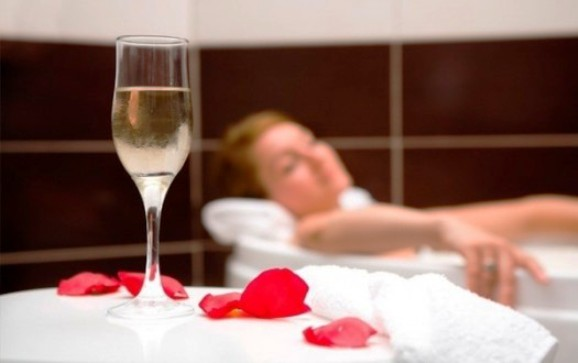 Женщина в ванной с бокалом шампанского