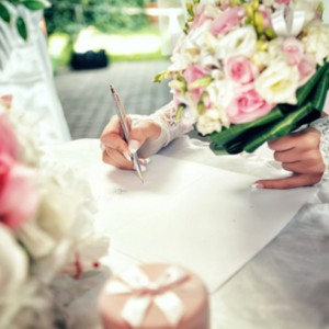 Bride signs up document on civil wedding ceremony.