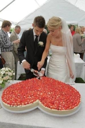 Жених и невеста разрезают свадебный торт в виде сердца