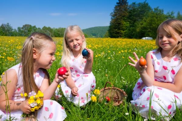 Три девочки на лугу играют пасхальными яйцами