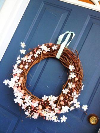 Пасхальный венок с цветами и яйцами на синей двери