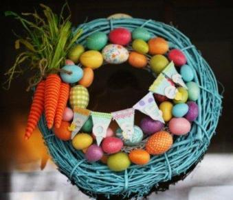 Пасхальный венок голубого цвета с пасхальными яйцами и пучком моркови и