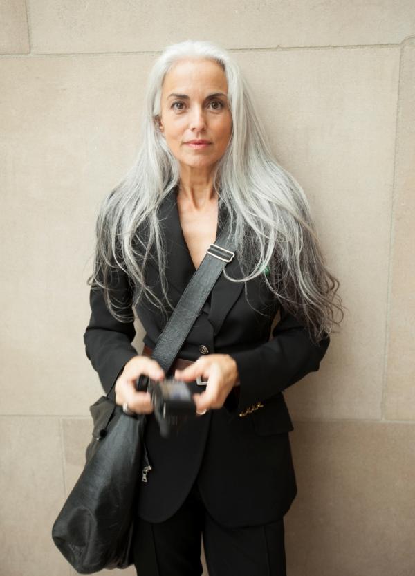 Ясмина Росси в черном брючном костюме, с сумкой через плечо