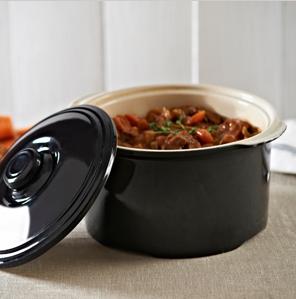Керамическая кастрюлька с крышкой темного цвета, наполненная запеченными овощами