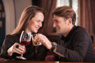Парень и девушка на свидании в ресторане с бокалами красного вина