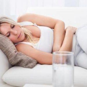 Женщина с болями в животе на диване