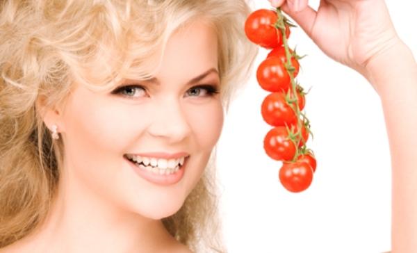 Юная девушка с веточкой томатов